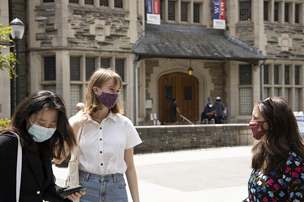 three women wearing mask smiles at each other in front of an old stone building