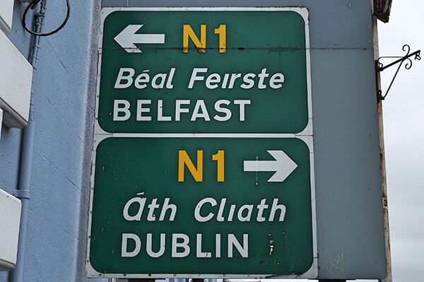 Two green N1 highway signs stacked on top of each other show arrows pointing the way to Belfast in the top sign and the way to Dublin in the bottom sign, with Belfast to the left and Dublin to the right