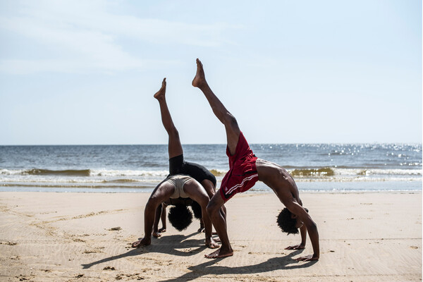 Three dancers doing back bands with one leg raised on a sunlit beach.