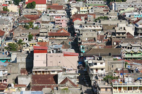 Aerial view of Cap Haitien, showing colorful, run down concrete buildings, shacks and palm trees