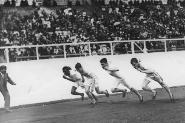John Baxter Taylor Jr., left, races three other competitors at the 1908 Summer Olympics in London. All four runners are wearing white shirts and shorts.