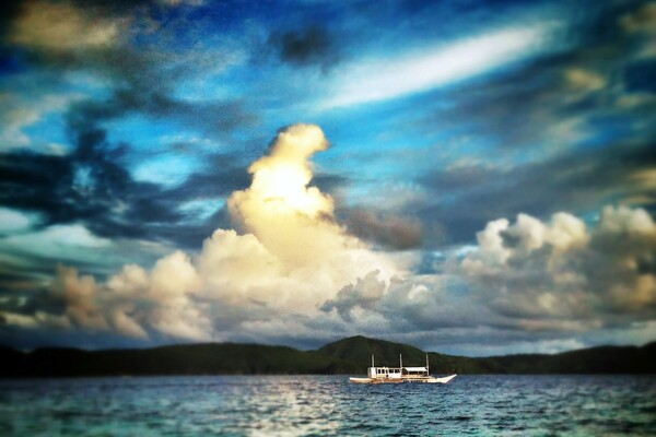 Palawan seascape and boat with clouds in distance