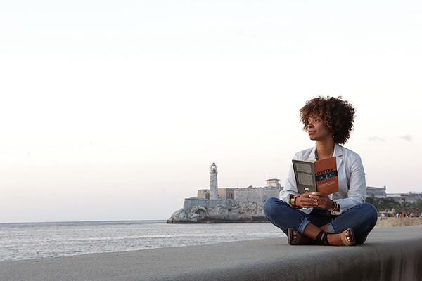 Amalia Dache sitting criss-cross applesauce on a sea wall in Cuba reading a book.