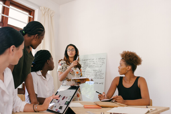 One person stands before a table with four other people, they are writing on a whiteboard while the other four people take notes and hold tablets.