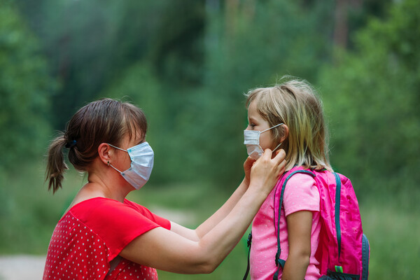Adult wearing mask adjusts the mask of a young child