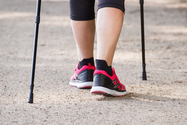 Closeup of person's calves, wearing running shoes accompanied with walking sticks.