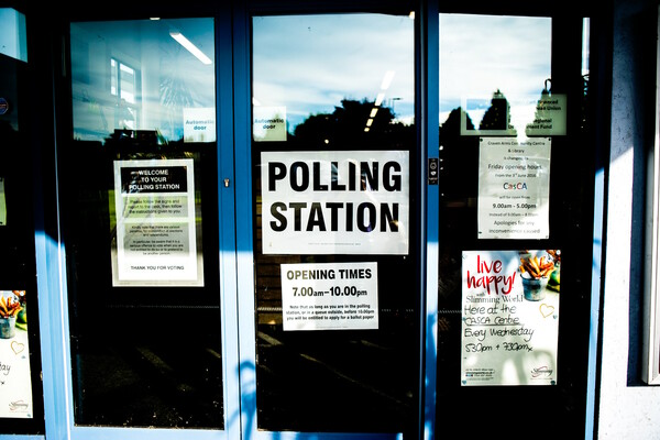 """Glass doors read """"polling station"""" with opening times listed"""