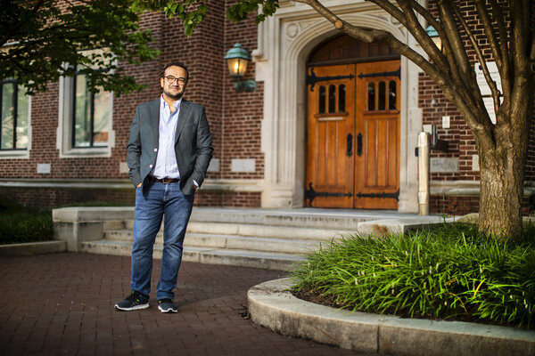 Hasan Küçük stands with his hands in his jeans pockets in front of the wooden double doors and red brick facade of  Fisher-Bennett Hall