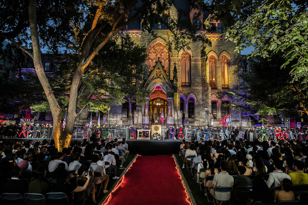 Front of College Hall lit up with red and blue lights during Convocation with students seated on lawn.