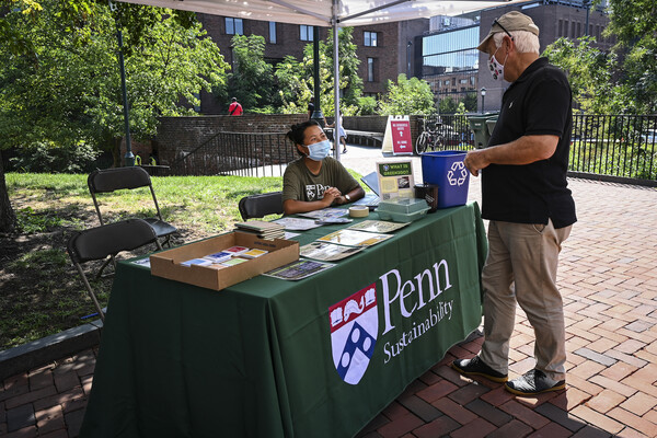 A person seated at a table labeled Penn Sustainability interacts with someone visiting the table
