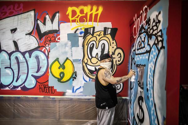 Artist spray-painting graffiti on wall of art gallery