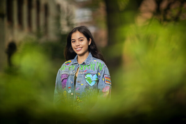 """A college-age person standing outside, with greenery blurred in the front of the image. She is wearing a jean jacket with the words """"Re-earth IN,"""" a globe in the shape of a heart, and other earth-related designs."""