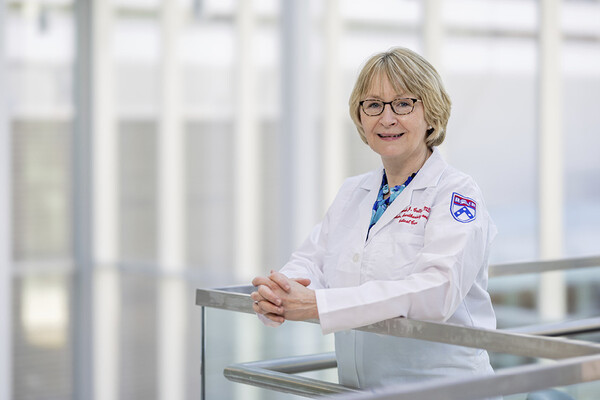 Deborah Culley standing by a railing at the Perelman School of Medicine in a white lab coat.