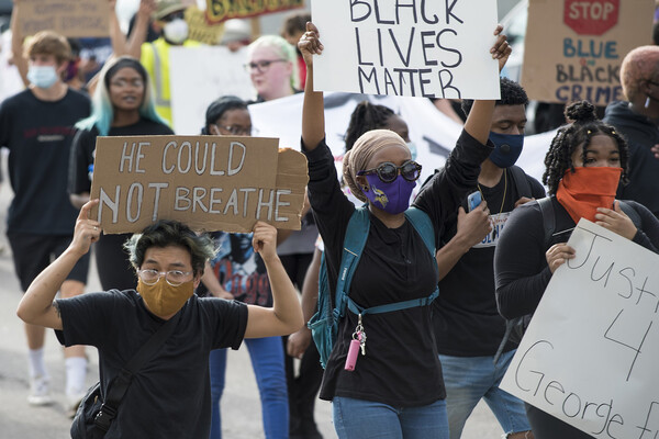 Masked people in a protest crowd holding signs that read Black Lives Matter, He Could Not Breathe, and Justice 4 George Floyd.