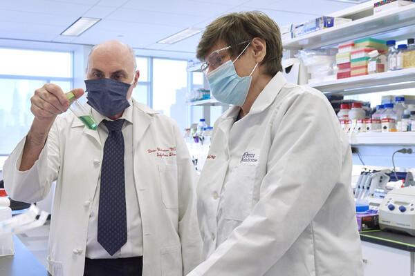 Drew Weisman and Katalin Kariko wear masks in a lab and look at liquid in a test tube.