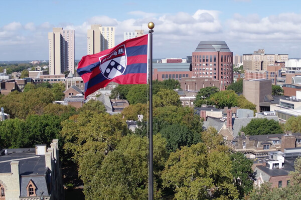 University of Pennsylvania flag flying with campus and the city of Philadelphia in the background.