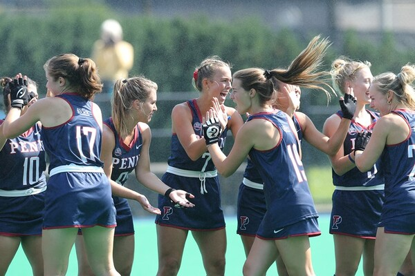 Members of the field hockey team high-five each other before a game.