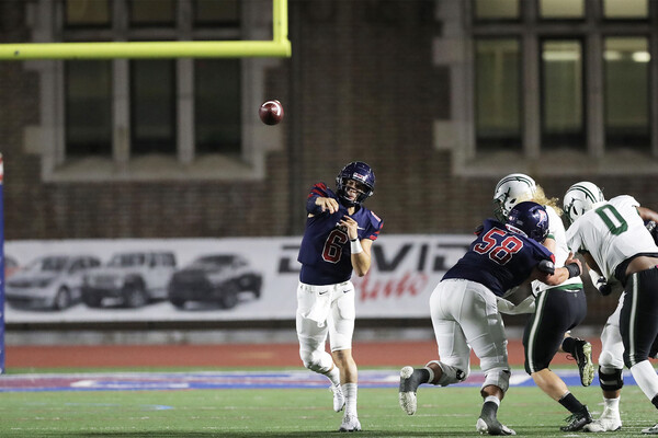 At Franklin Field, quarterback John Quinnelly throws the ball down field, while being rushed by a defender.