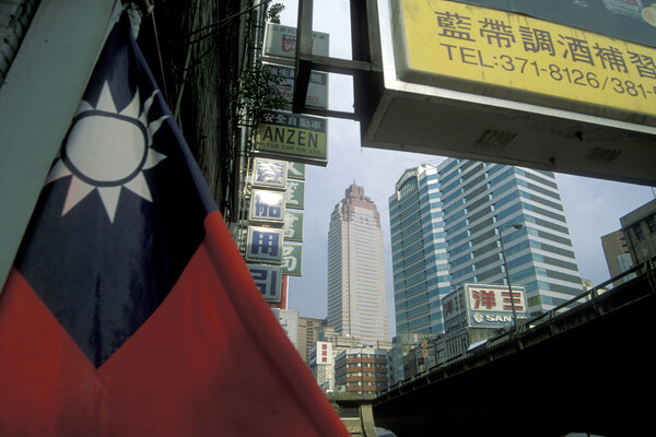 a taiwanese flag is in the foreground with skyscrapers and shop signs in Chinese and English in the background