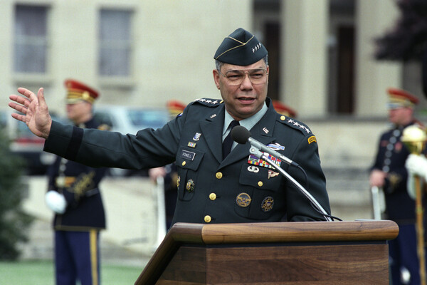 Colin Powell, wearing full military garb and standing at a brown wooden podium with a microphone, gestures to his right, sweeping his arm that direction